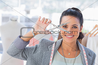 Attractive designer holding scissors in front of her face