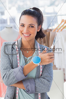 Attractive designer with measuring tape holding scissors