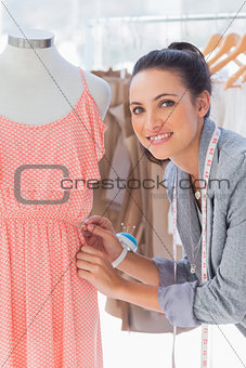Attractive fashion designer adjusting dress