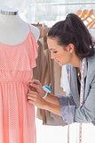 Pretty fashion designer fixing dress