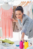 Beautiful fashion designer adjusting dress