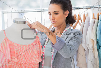 Attractive designer adjusting,dress on a mannequin