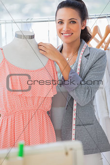 Smiling fashion designer adjusting dress