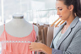 Fashion designer measuring dress