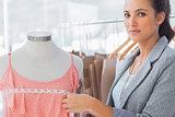 Pretty fashion designer measuring dress