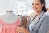 Smiling fashion designer measuring dress