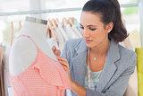Fashion designer measuring dress in a studio