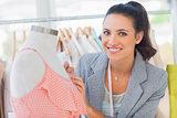 Smiling fashion designer measuring dress on a mannequin