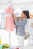 Attractive designer fixing dress on a mannequin