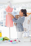 Attractive designer adjusting dress on a mannequin