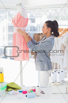 Attractive designer adjusting dress on a mannequin