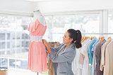 Pretty fashion designer adjusting dress