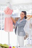 Cheerful fashion designer measuring dress on a mannequin