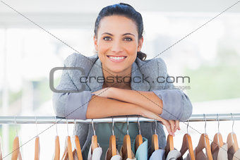 Attractive fashion designer leaning on clothes