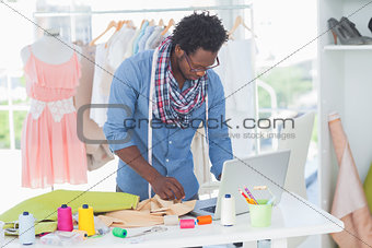 Attractive fashion designer working on laptop