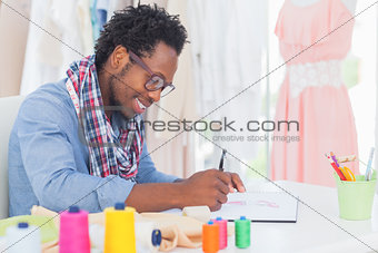 Attractive fashion designer sitting at his desk drawing