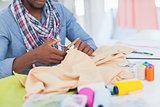 Fashion designer cutting textile