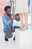 Attractive fashion designer adjusting a dress