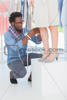 Attractive fashion designer adjusting a dress
