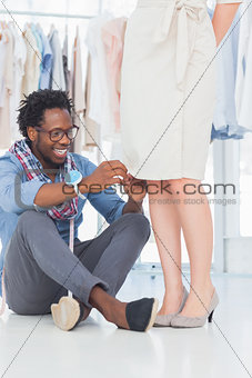 Attractive fashion designer fixing needles on dress