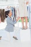 Pretty fashion designer adjusting dress on a model