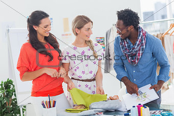 Three fashion designers looking at sketchpad