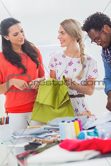 Three fashion designers holding textile