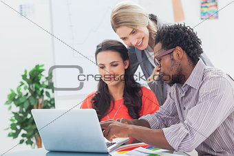 Three designers working together on a laptop