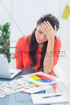 Annoyed designer sitting behind her desk