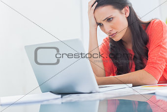 Confused designer looking at her laptop