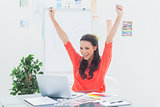 Excited woman raising her arms while working on her laptop