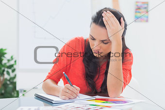 Tired designer holding her head while she is drawing