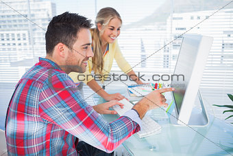 Pair of photo editors working together on a computer