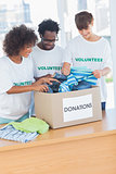 Cheerful volunteers looking at clothes from a donations box