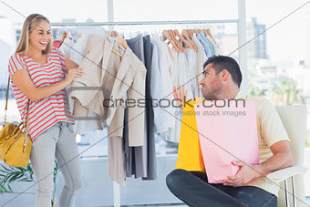 Depressed man looking at his shopaholic girlfriend