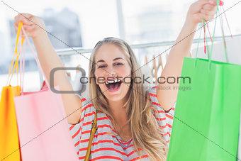 Blonde woman raising shopping bags
