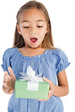 Surprised little girl holding a wrapped gift