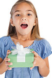 Excited little girl holding a wrapped gift