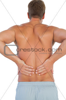 Shirtless man suffering from lower back pain