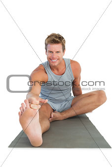 Cheerful man stretching his leg on the floor