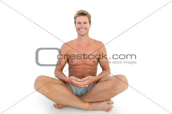 Cheerful man with eyes closed meditating on the floor