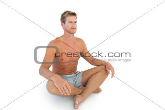 Handsome man doing yoga and sitting in lotus position