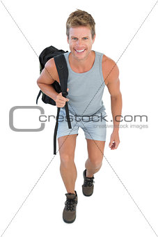 Cheerful man holding backpack