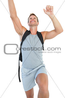 Man holding backpack and climbing