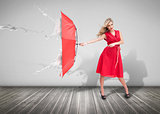 Attractive woman holding an umbrella to protect herself from the rain