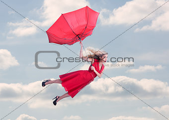 Attractive woman flying in the blue sky