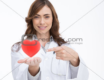 Doctor holding and pointing at a red heart