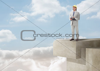 Architect standing on a building over the clouds