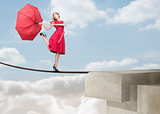 Pretty woman walking on a rope over the clouds