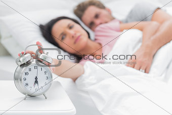 Woman turning off the alarm clock